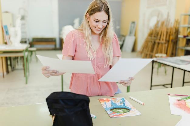 Souriante jeune femme regardant des peintures debout derrière la table
