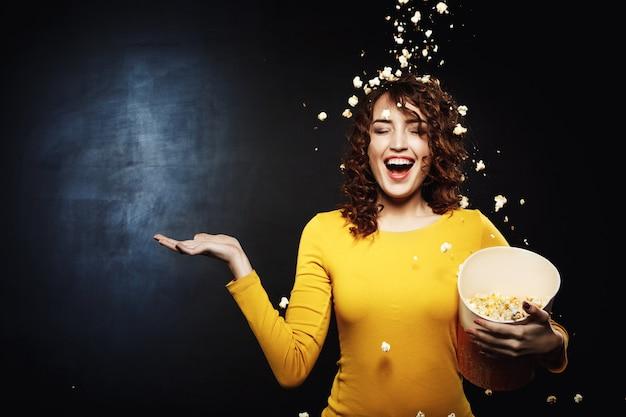 Souriante jeune femme restant sous une douche à pop-corn avec la main droite vers le haut