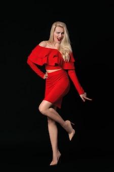 Souriante jeune femme en robe rouge posant