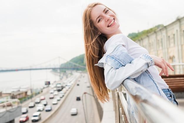 Souriante jeune femme s'appuyant sur une rampe métallique en regardant la caméra