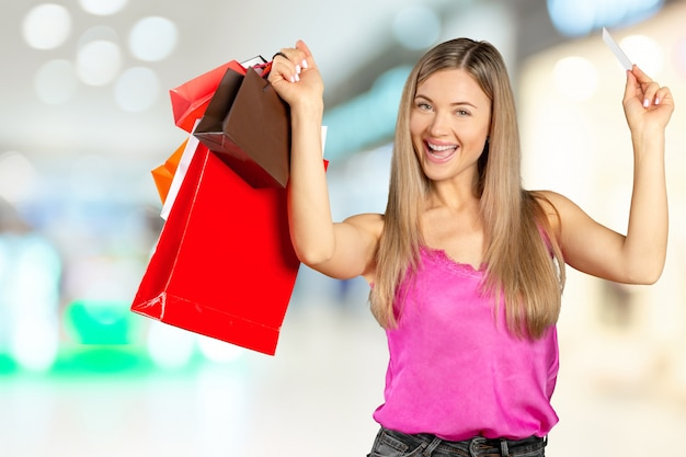 Souriante jeune femme avec des sacs à provisions sur fond de centre commercial
