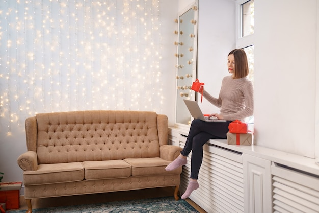Souriante jeune femme saluant des amis avec noël en chat vidéo sur ordinateur portable avec des coffrets cadeaux