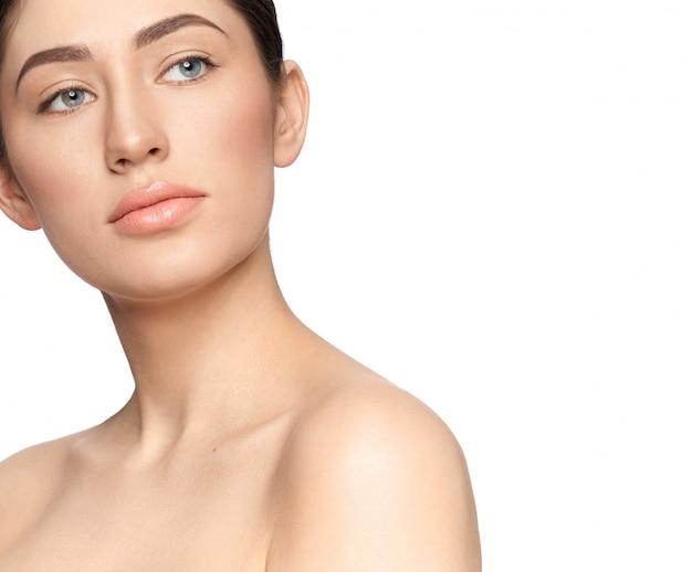 Souriante jeune femme sans maquillage à côté en studio