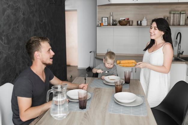 Souriante jeune femme servant du maïs cuit à la vapeur à sa famille au petit déjeuner