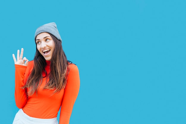 Souriante jeune femme avec signe ok portant chapeau tricoté devant fond bleu