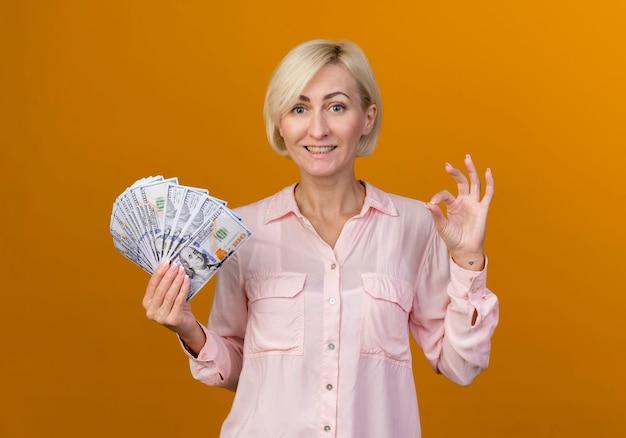 Souriante jeune femme slave blonde tenant de l'argent et montrant le geste okey isolé sur un mur orange