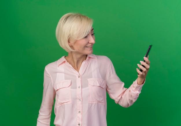Souriante jeune femme slave blonde tenant et lookign au téléphone mobile isolé sur fond vert