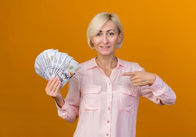 Souriante jeune femme slave blonde tenant et points à l'argent isolé sur mur orange