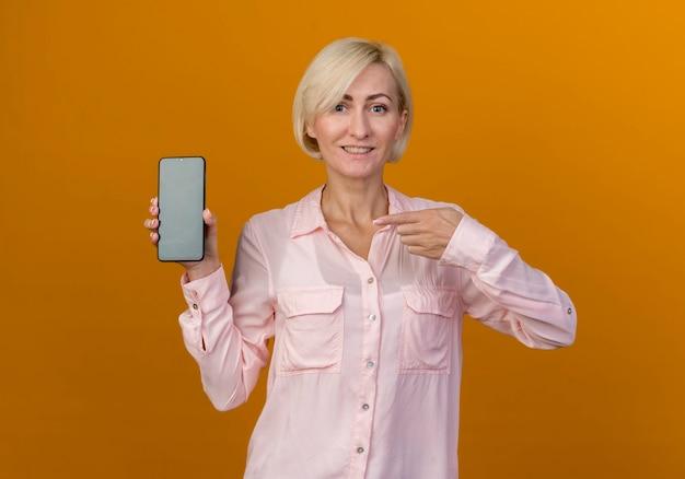 Souriante jeune femme slave blonde tenant et points au téléphone isolé sur mur orange