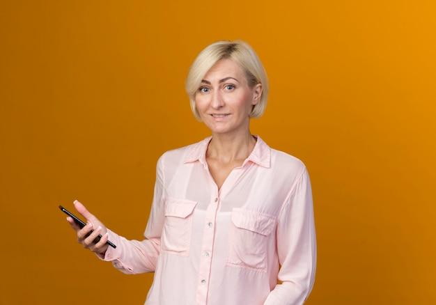Souriante jeune femme slave blonde tenant un téléphone isolé sur un mur orange