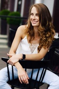 Souriante jeune femme avec smartwatches se détendre et assis sur une chaise à l'extérieur