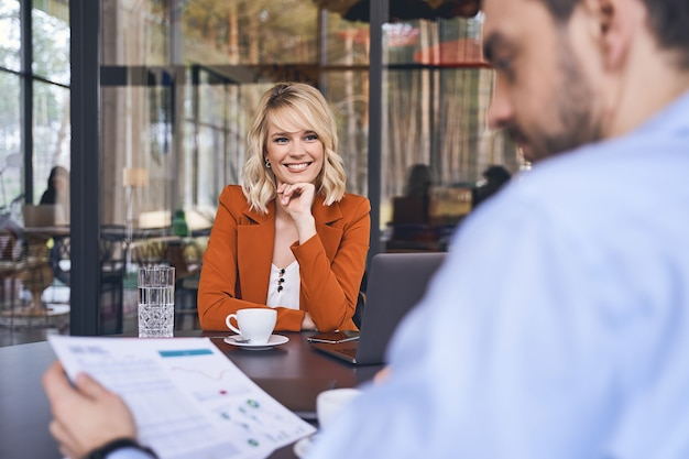 Souriante jeune femme avec son menton appuyé sur sa main regardant son collègue masculin