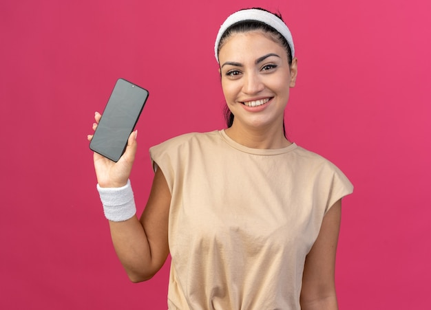 Souriante jeune femme sportive caucasienne portant un bandeau et des bracelets regardant à l'avant montrant un téléphone portable à une caméra isolée sur un mur rose