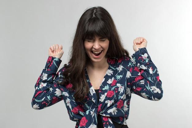 Souriante jeune femme en t-shirt conçu de bonne humeur aux cheveux longs sur blanc