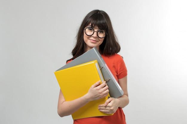 Souriante jeune femme en t-shirt conçu de bonne humeur tenant des fichiers colorés aux cheveux longs sur blanc