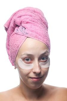 Souriante jeune femme avec des taches blanches sous les yeux et une serviette rose sur la tête isolée sur blanc. closeup portrait. soin de la peau