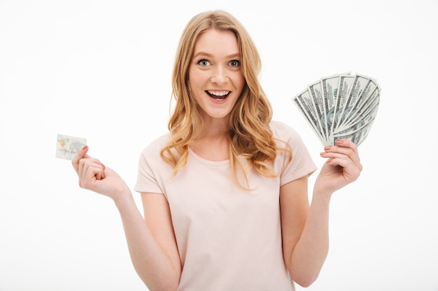Souriante jeune femme tenant argent et carte de crédit.