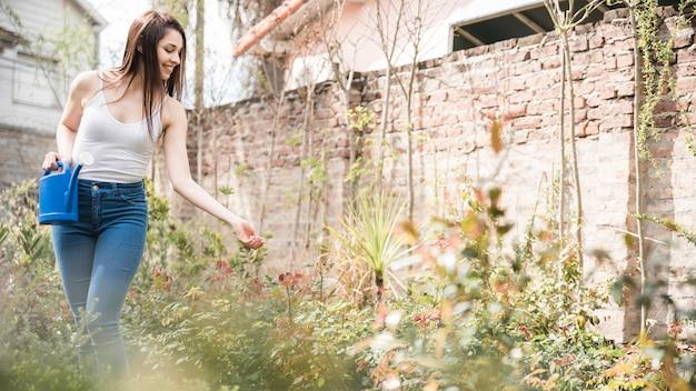 Souriante jeune femme tenant un arrosoir à la main en prenant soin des plantes dans le jardin
