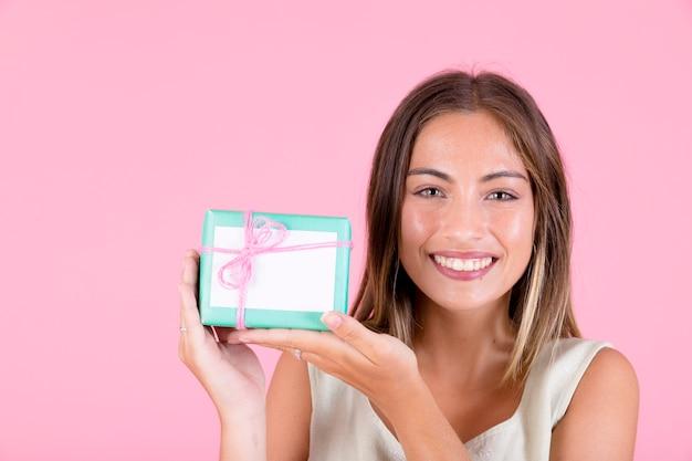 Souriante jeune femme tenant une boîte cadeau attachée avec du fil rose