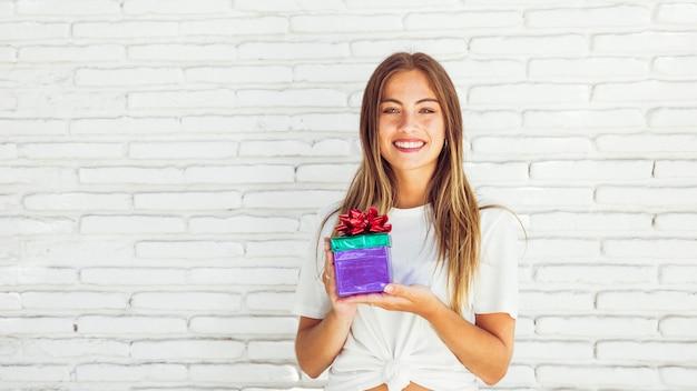 Souriante jeune femme tenant une boîte cadeau devant le mur de briques