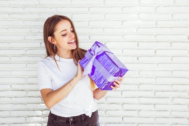 Souriante jeune femme tenant une boîte cadeau