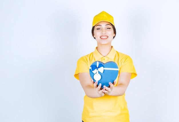 Souriante jeune femme tenant une boîte en forme de coeur sur un mur blanc