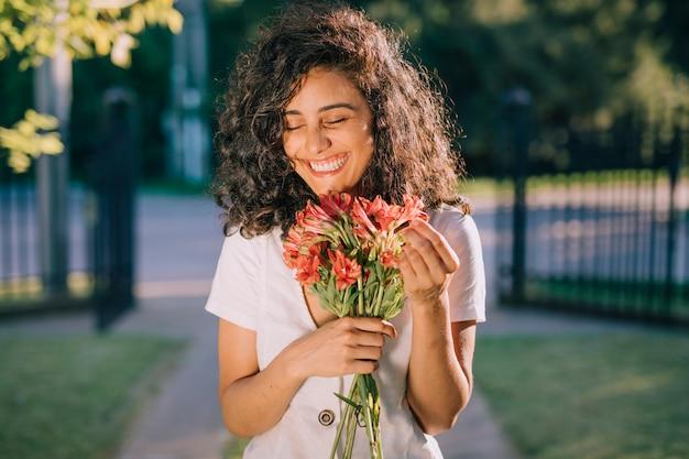Souriante jeune femme tenant un bouquet de fleurs à la main
