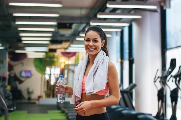 Souriante jeune femme tenant une bouteille d'eau dans une salle de sport.