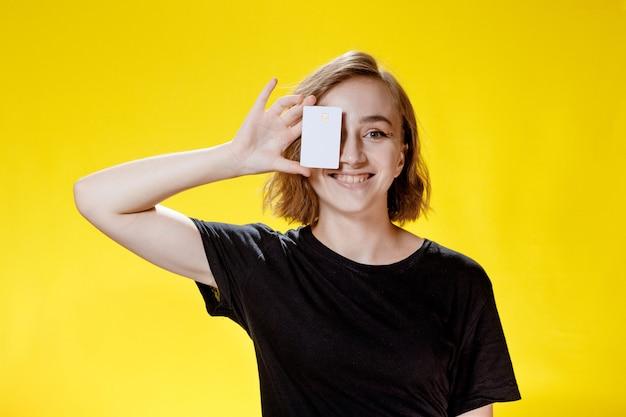 Souriante jeune femme tenant une carte de crédit sur fond jaune.