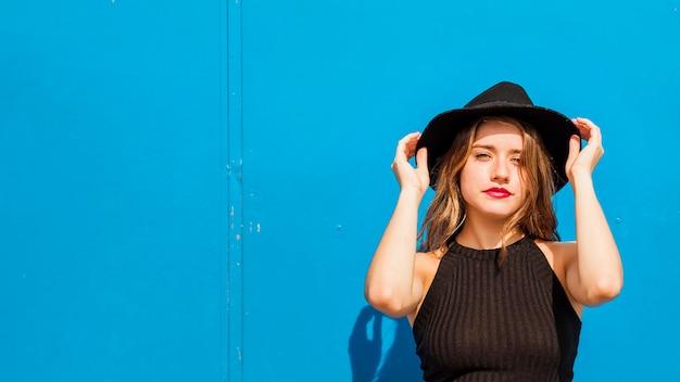 Souriante jeune femme tenant un chapeau noir sur la tête