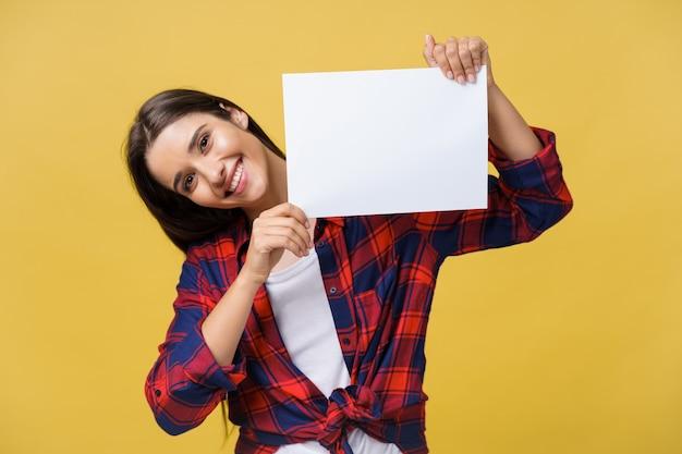 Souriante jeune femme tenant une feuille de papier blanc. portrait en studio sur fond jaune.