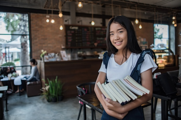 Souriante jeune femme tenant des livres