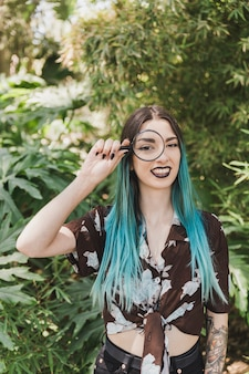 Souriante jeune femme tenant une loupe sur ses yeux