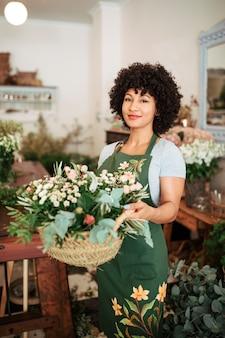 Souriante jeune femme tenant un panier de fleurs dans un magasin de fleurs