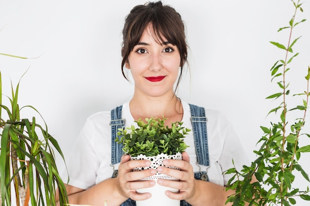 Souriante jeune femme tenant une plante en pot