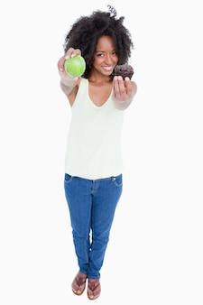 Souriante jeune femme tenant une pomme dans une main et un muffin dans l'autre