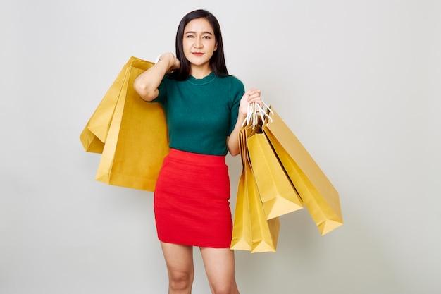Souriante jeune femme tenant des sacs à provisions