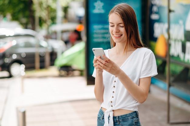 Souriante jeune femme tenant un smartphone et regardant l'écran debout en plein air