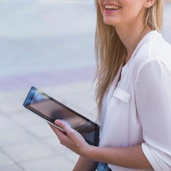 Souriante jeune femme tenant une tablette numérique