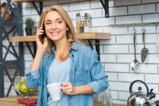 Souriante jeune femme tenant une tasse blanche à la main, parler au téléphone mobile