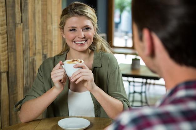 Souriante jeune femme tenant une tasse de café tout en regardant l'homme au café
