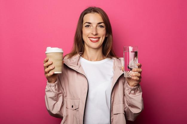 Souriante jeune femme tenant une tasse en papier et une tasse en verre avec de l'eau sur une surface rose