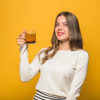 Souriante jeune femme tenant une tasse de thé à base de plantes dans la main debout sur fond jaune