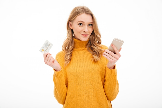 Souriante jeune femme tenant un téléphone mobile et une carte de crédit.