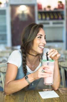 Souriante jeune femme tenant un verre de lait frappé avec du papier de soie sur la table
