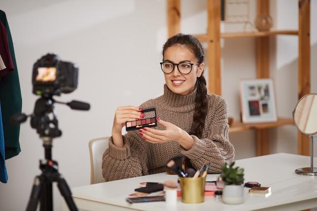 Souriante jeune femme testant des produits de maquillage pour la vidéo