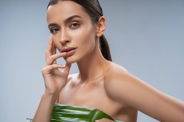 Souriante jeune femme utilisant une feuille verte comme soutien-gorge