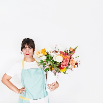 Souriante jeune femme avec vase à fleur sur fond blanc