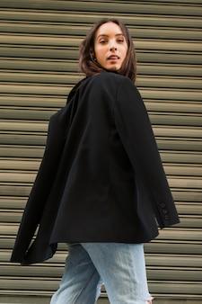 Souriante jeune femme avec une veste noire devant un volet de fer