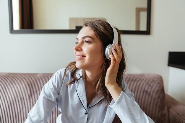 Souriante jeune femme vêtue de pyjama écouter de la musique